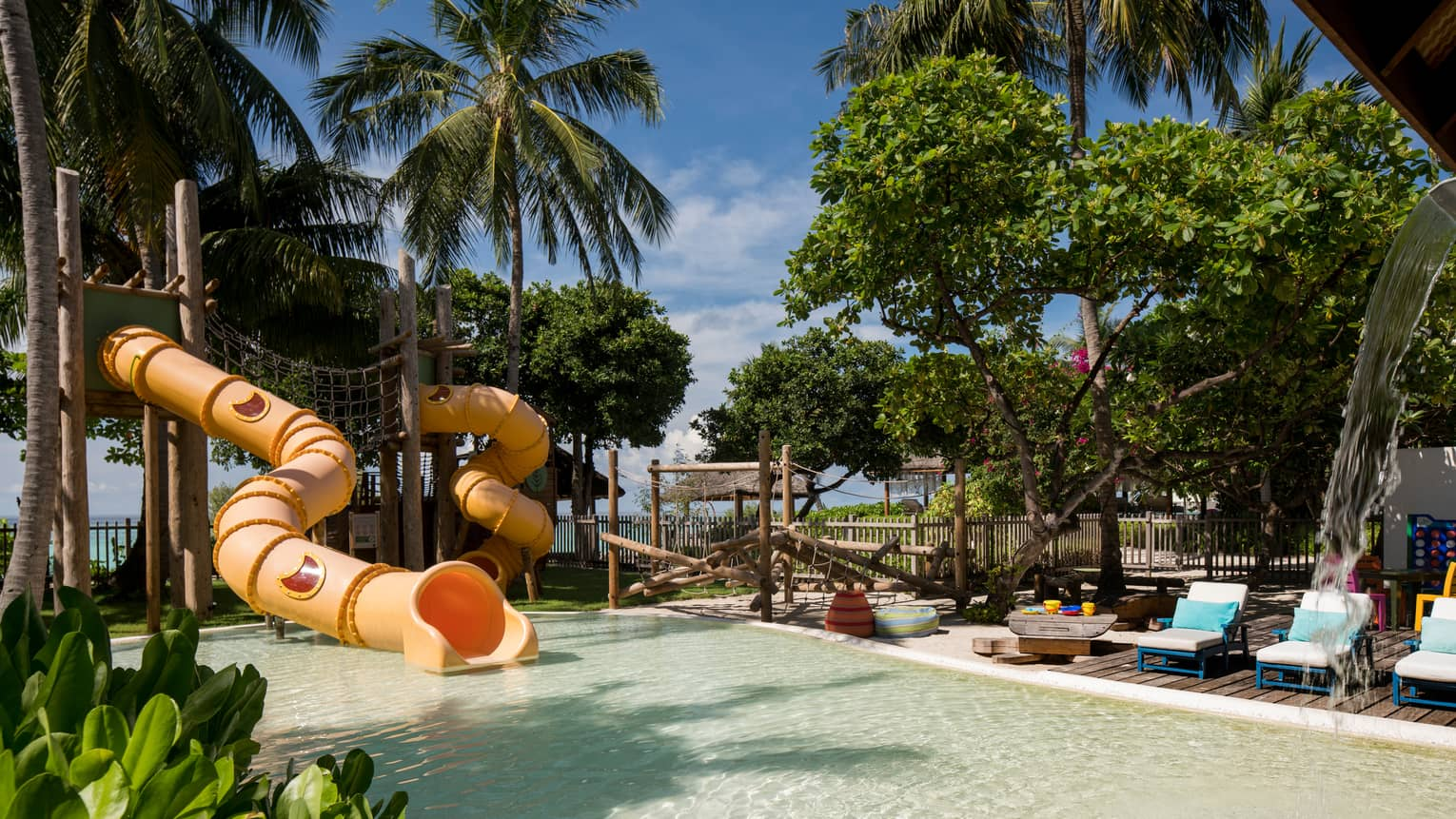 Kids Club children's pool with winding yellow water slide under palm trees