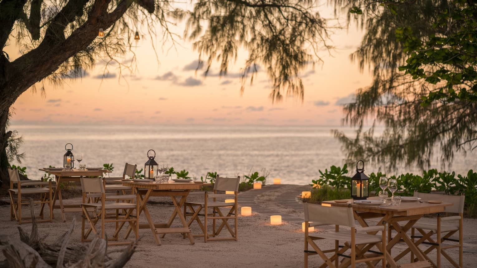 Outdoor wooden tables and chairs on sand at dusk with lit candles lining path to the ocean