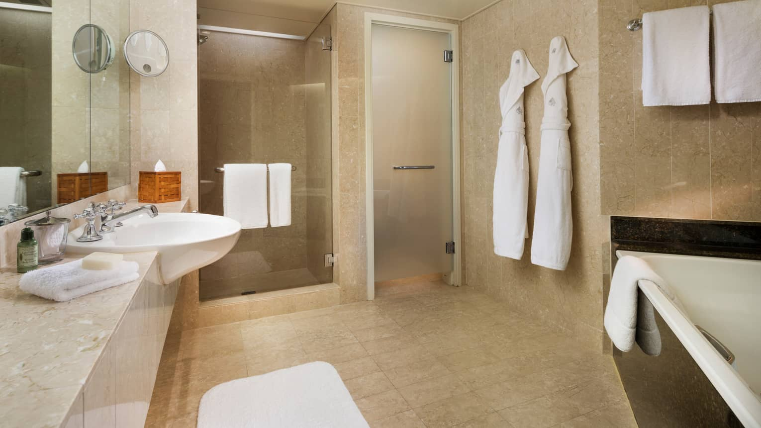 Hotel Suite full marble bathroom, two white robes hang by glass walk-in showers, sink