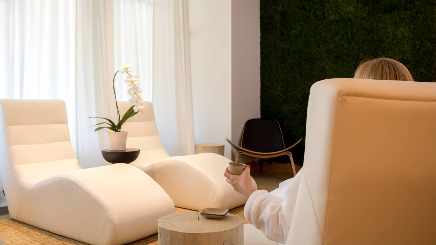 Back of woman in white robe sitting in white spa lounge chair holding small tea cup, two empty chairs across