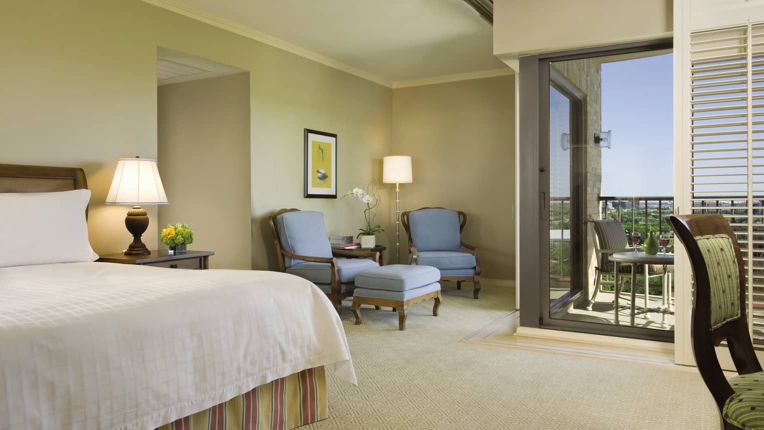 Corner Tower Room side of bed, two blue armchairs and ottoman, glass patio door