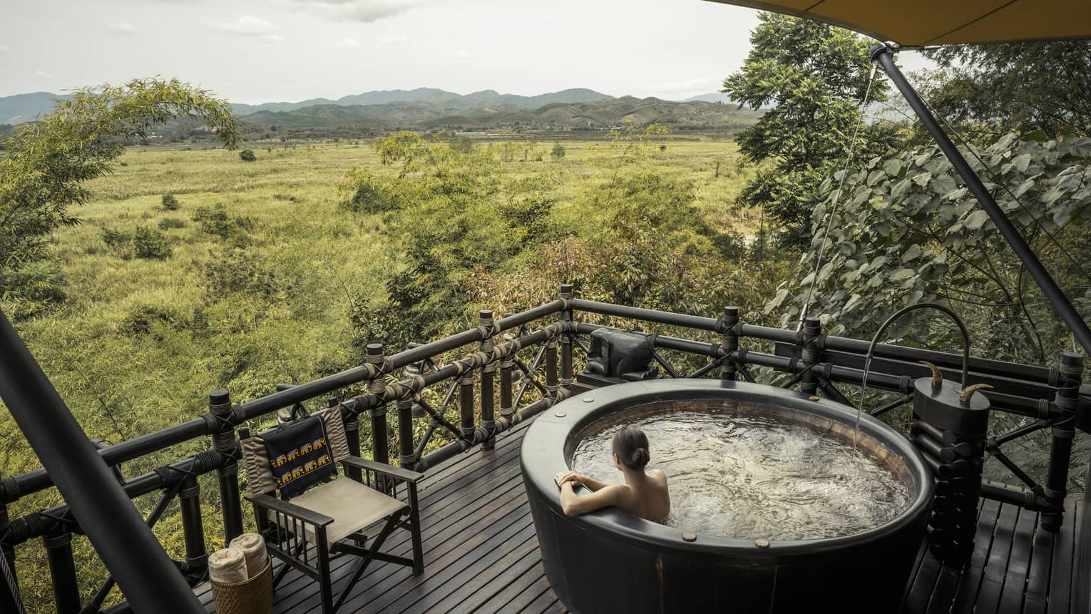 Woman wades in large round hot tub on wood deck overlooking green field, mountains