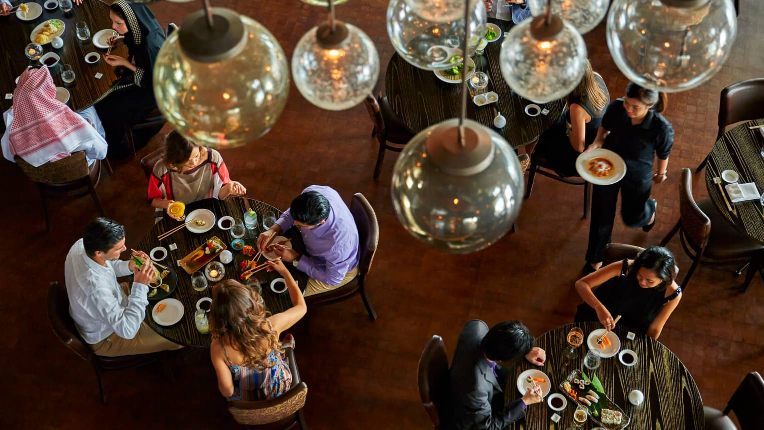 Aerial view of gold lamps, guests around tables in Nobu Doha's main dining room