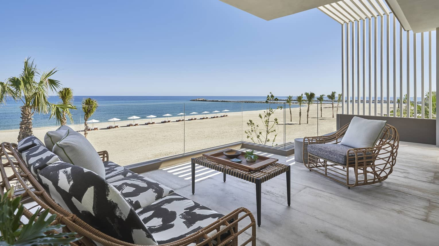 Outdoor terrace with modern wicker sofa and arm chair, glass railing, beach and ocean view
