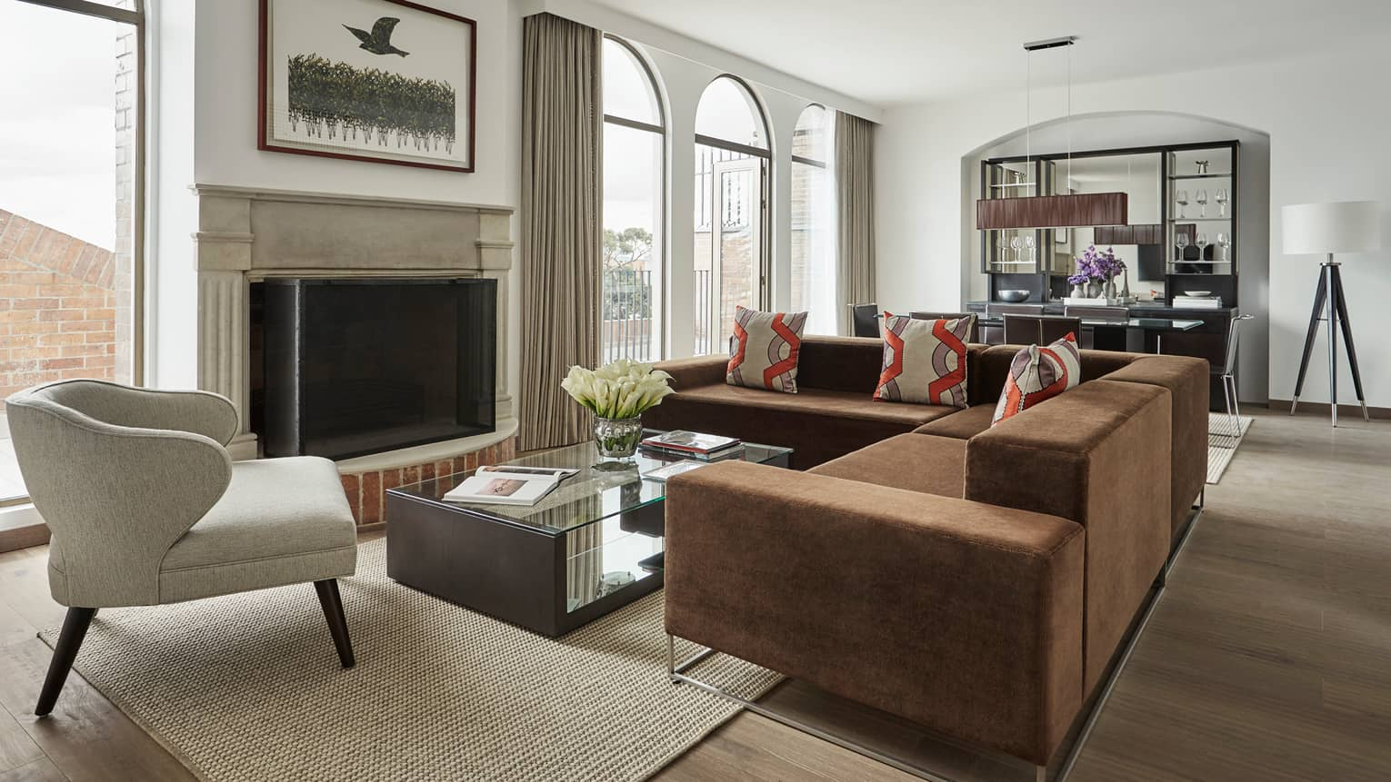 Penthouse Suite living room with L-shaped brown sofa, white armchair, glass coffee table, fireplace