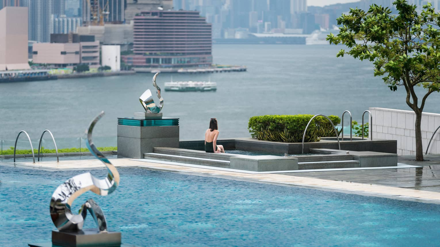 Woman in swimsuit sits on edge of swimming pool on patio near modern silver sculptures, waterfront