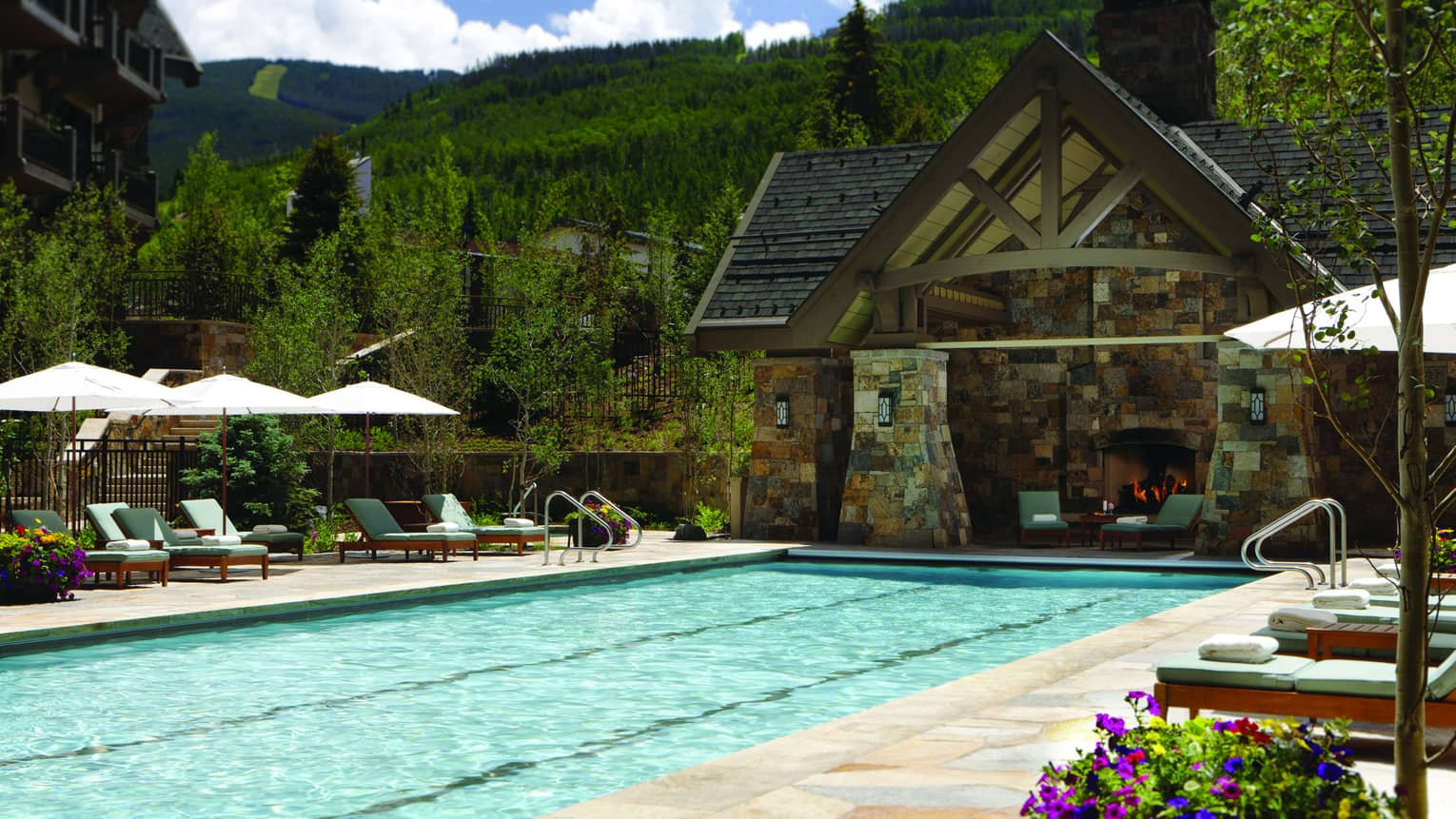 Outdoor lap pool at Four Seasons Resort Vail, lined with lounge chairs