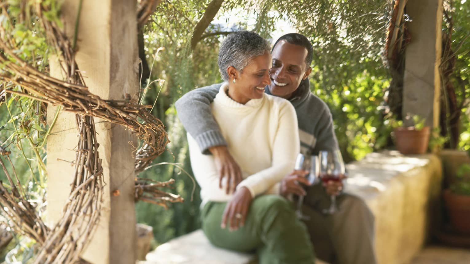 Smiling man and woman holding glasses of wine cuddle on stone bench beside wood post