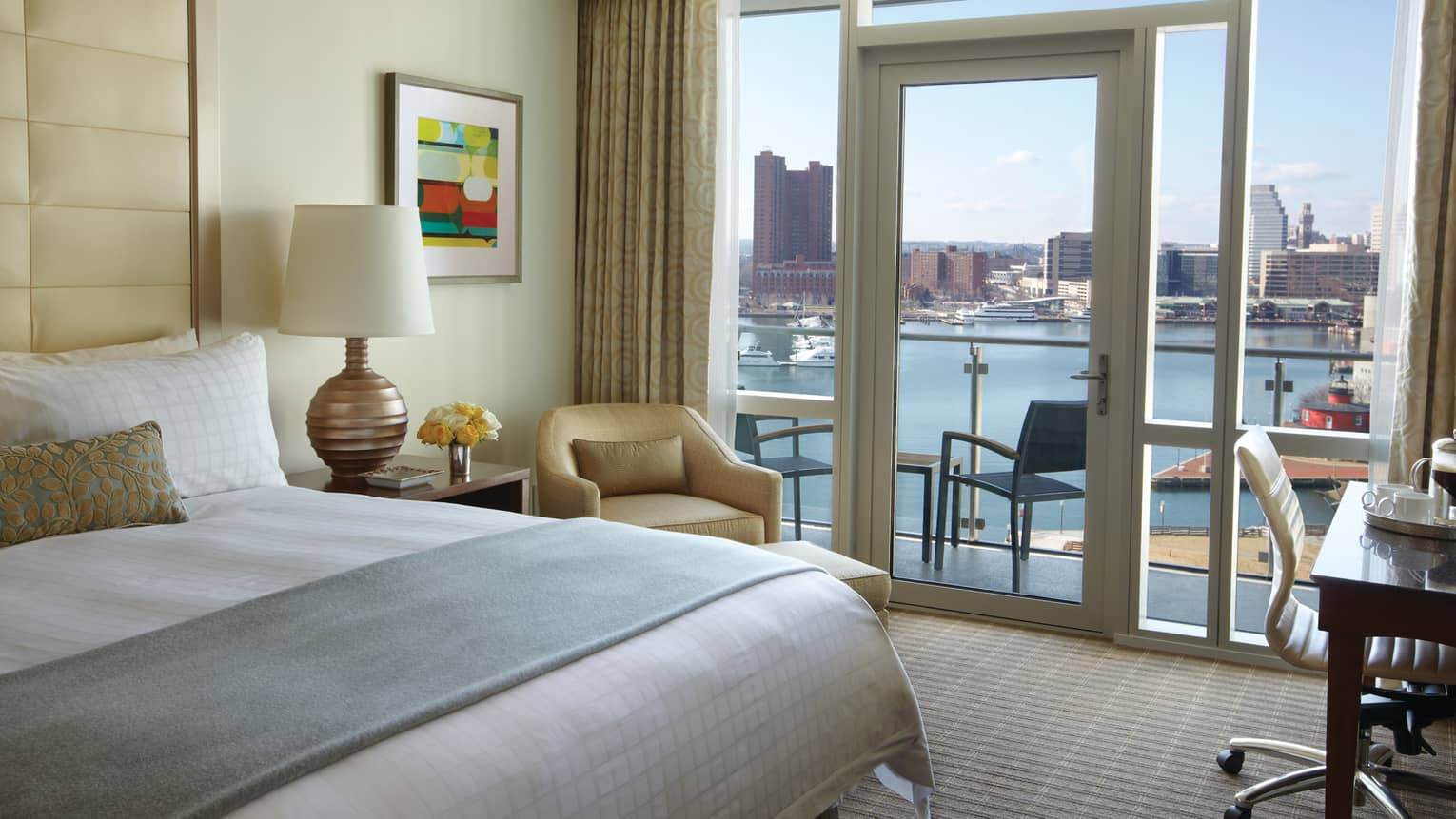 Edge of bed with folded blue blanket, armchair by glass door, balcony door, harbour view