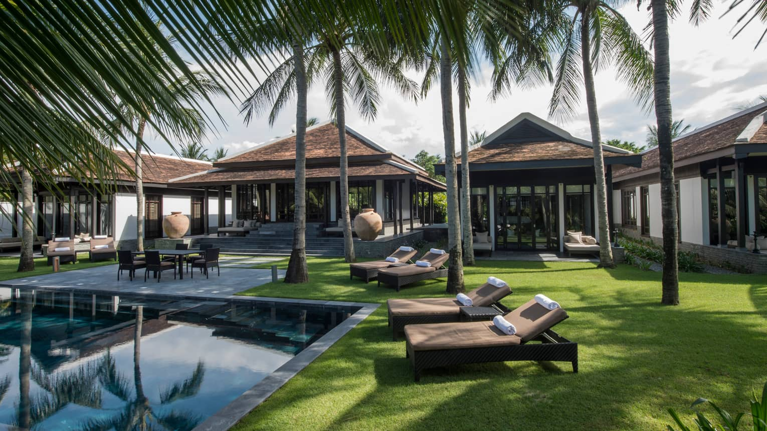 Three-bedroom Hilltop Villas, palm trees, lounge chairs on lawn around outdoor pool