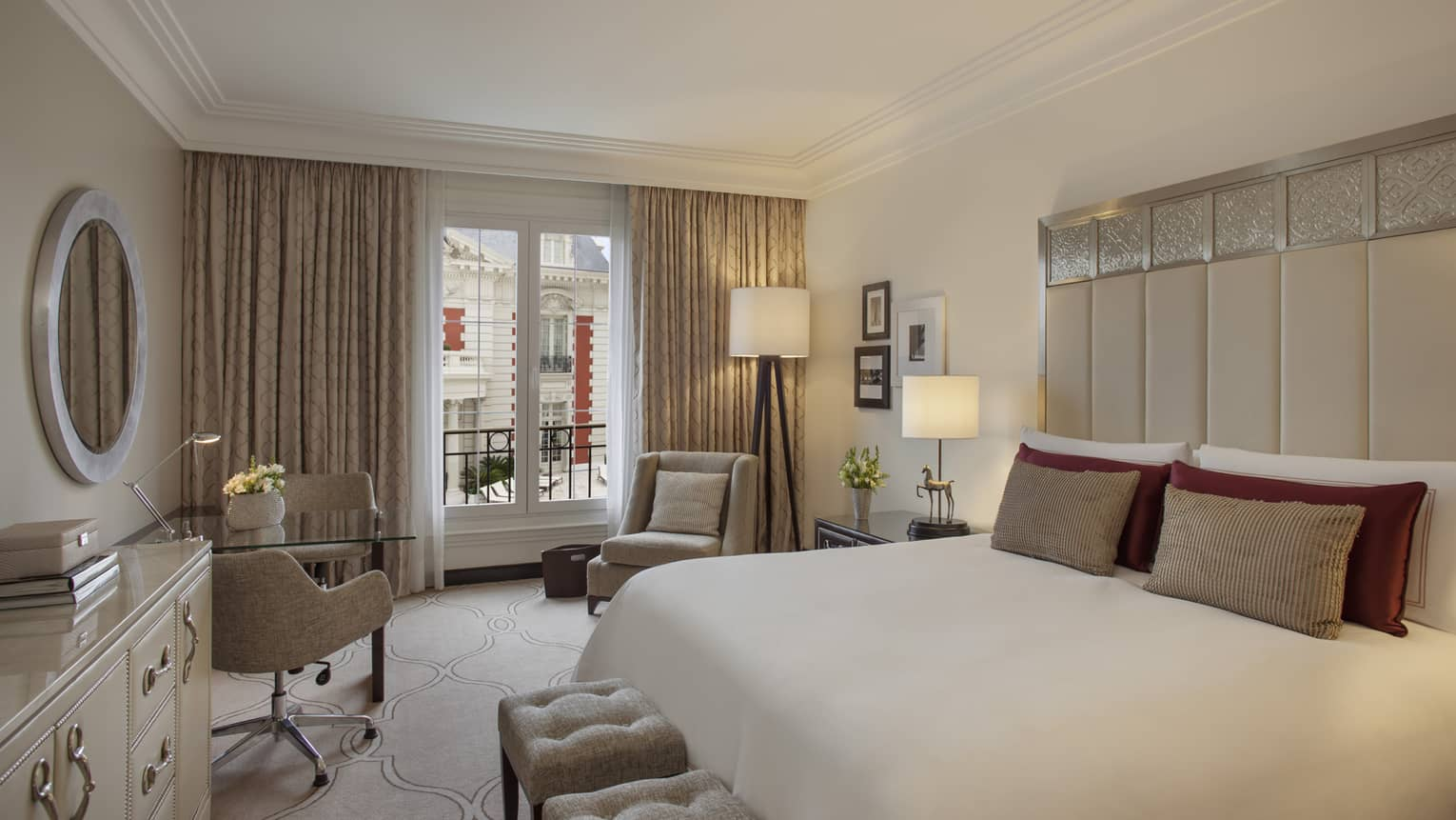 Mansion-View Room with clean, white-and-cream decor, tall padded headboard with silver details, white plush benches, chairs