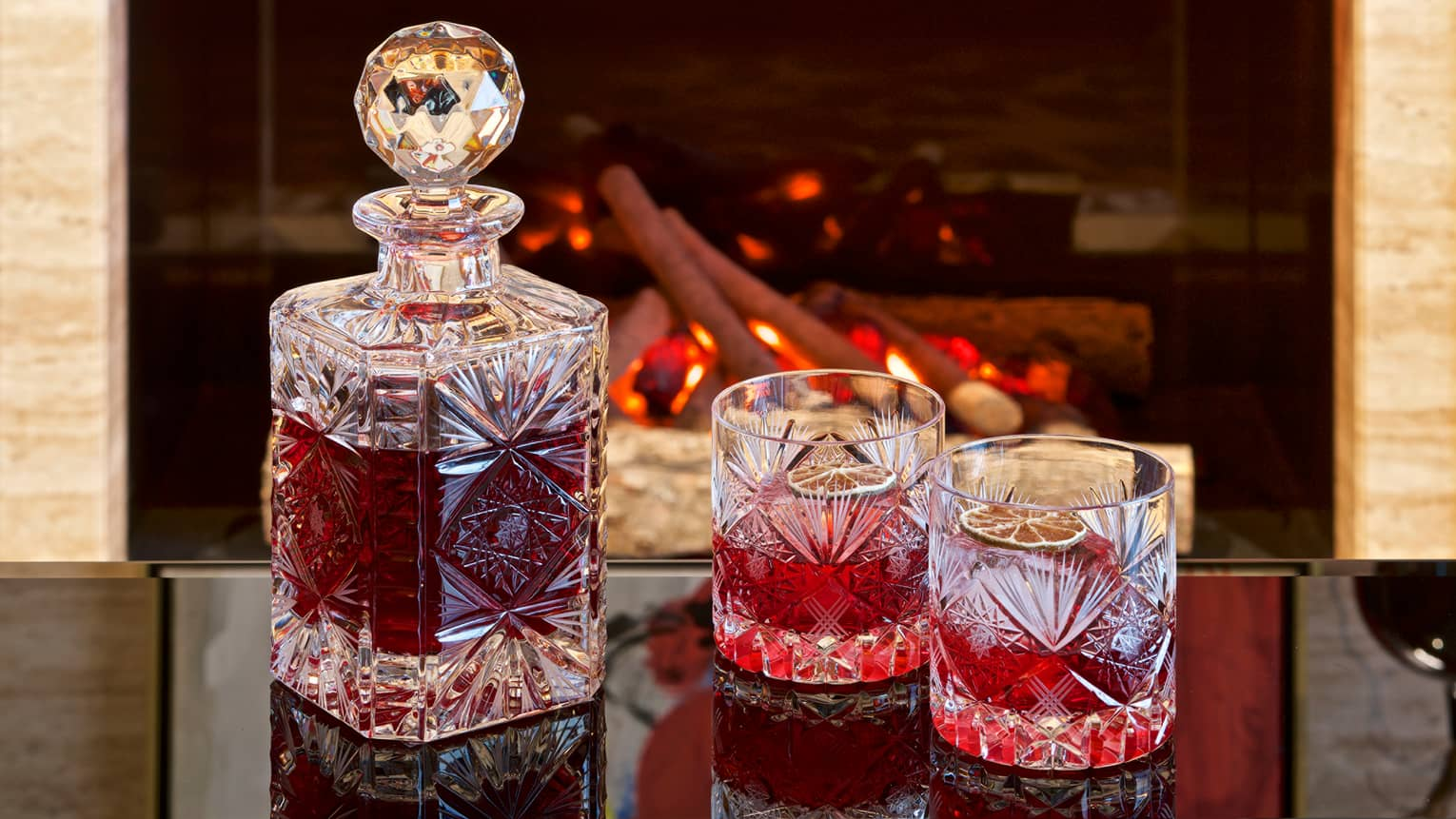 Cranberry-infused vodka in heavy crystal rocks glasses, decanter in front of fireplace