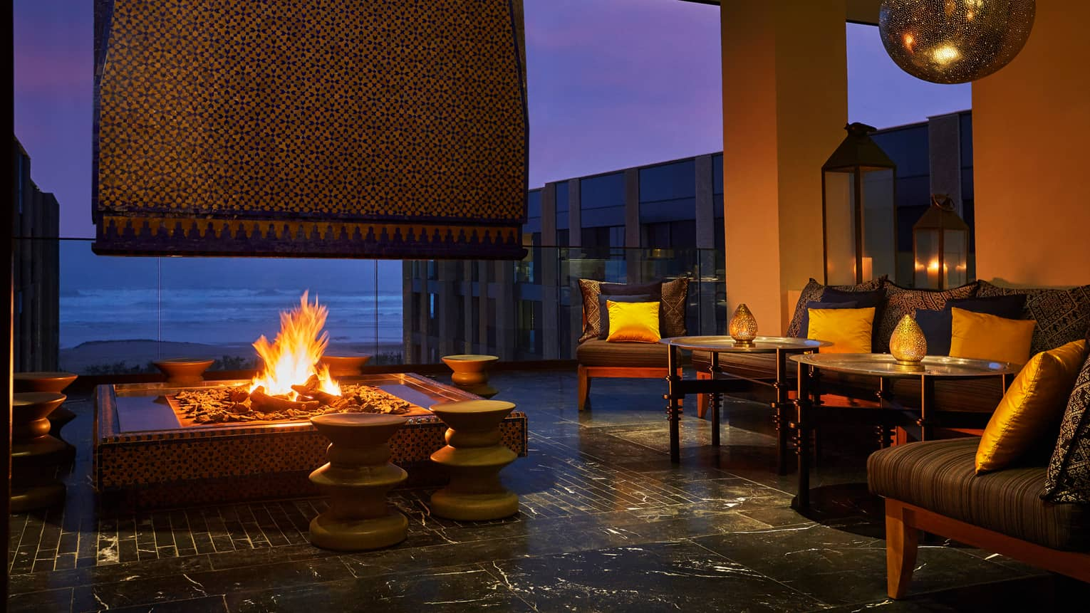 Patios sofas, beaches around large outdoor fireplace on Mint terrace at night