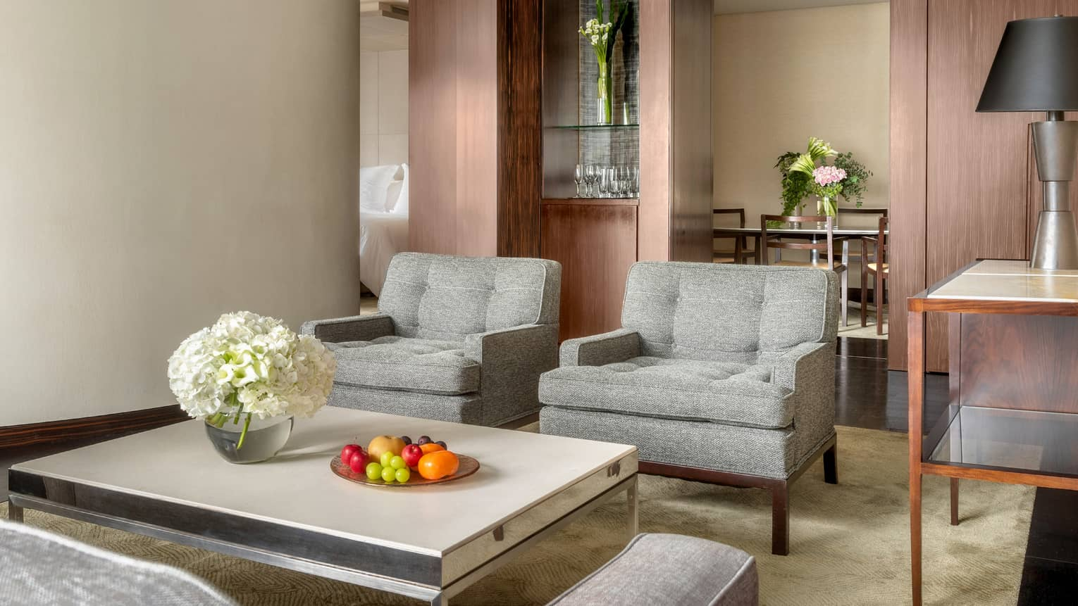 Deluxe One-Bedroom Suite living room vignette with gray club chairs and white coffee table