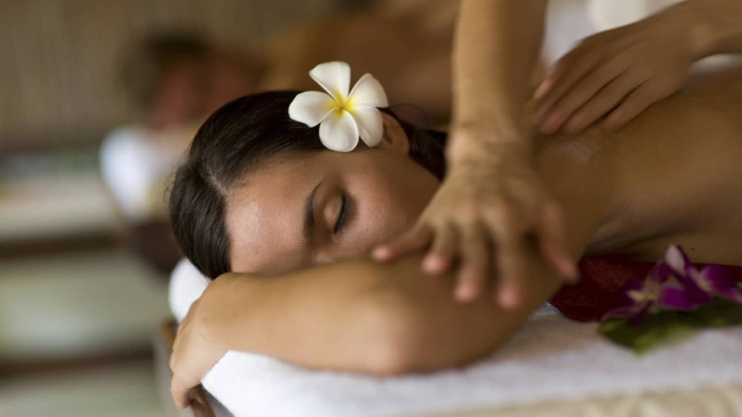 Woman with white flower in hair rests head, arms on spa massage table