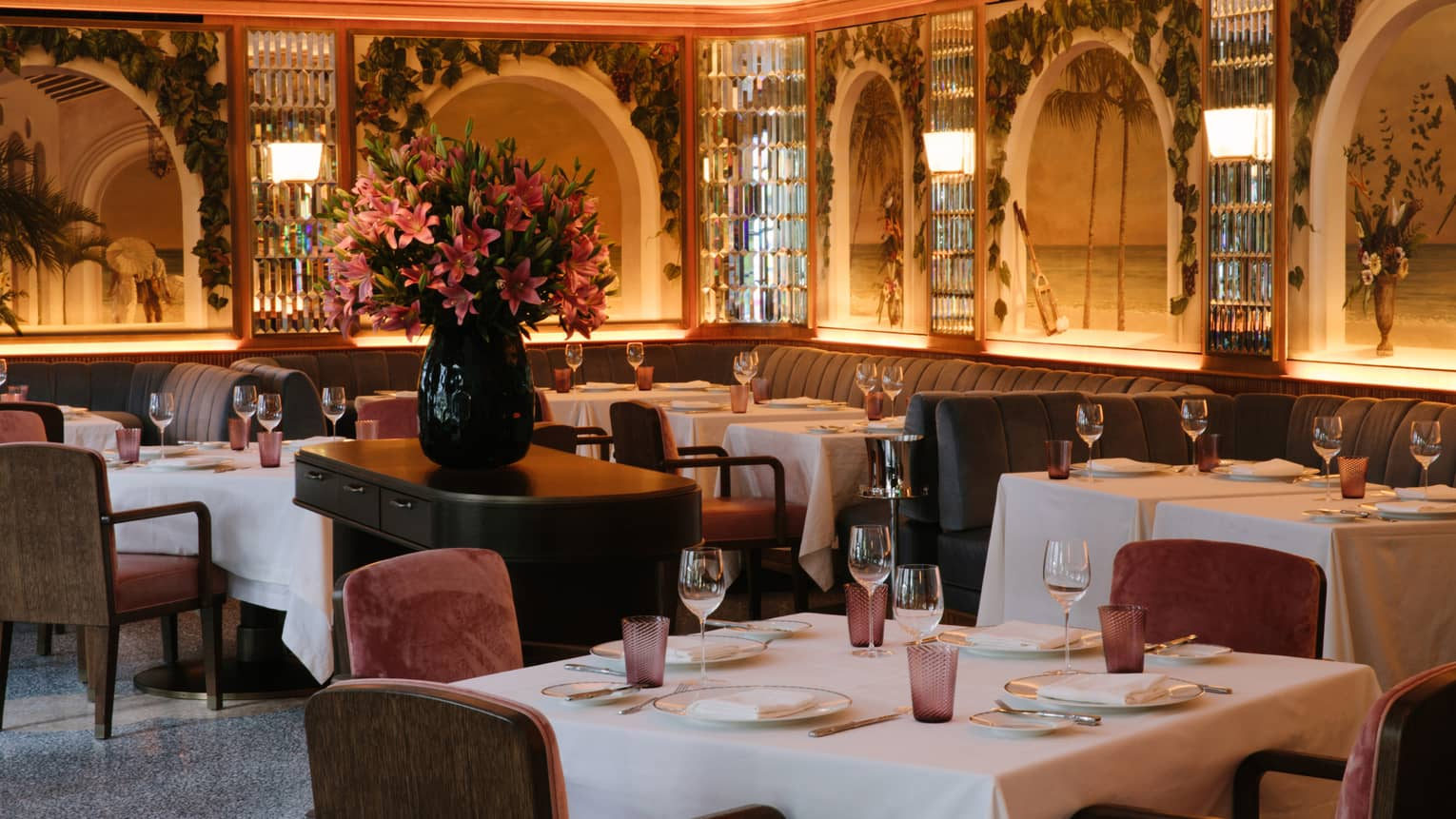 An empty dinning room of plush velvet chairs and tropical inspired murals. A large bouquet of pink hibiscus flowers sits in the middle