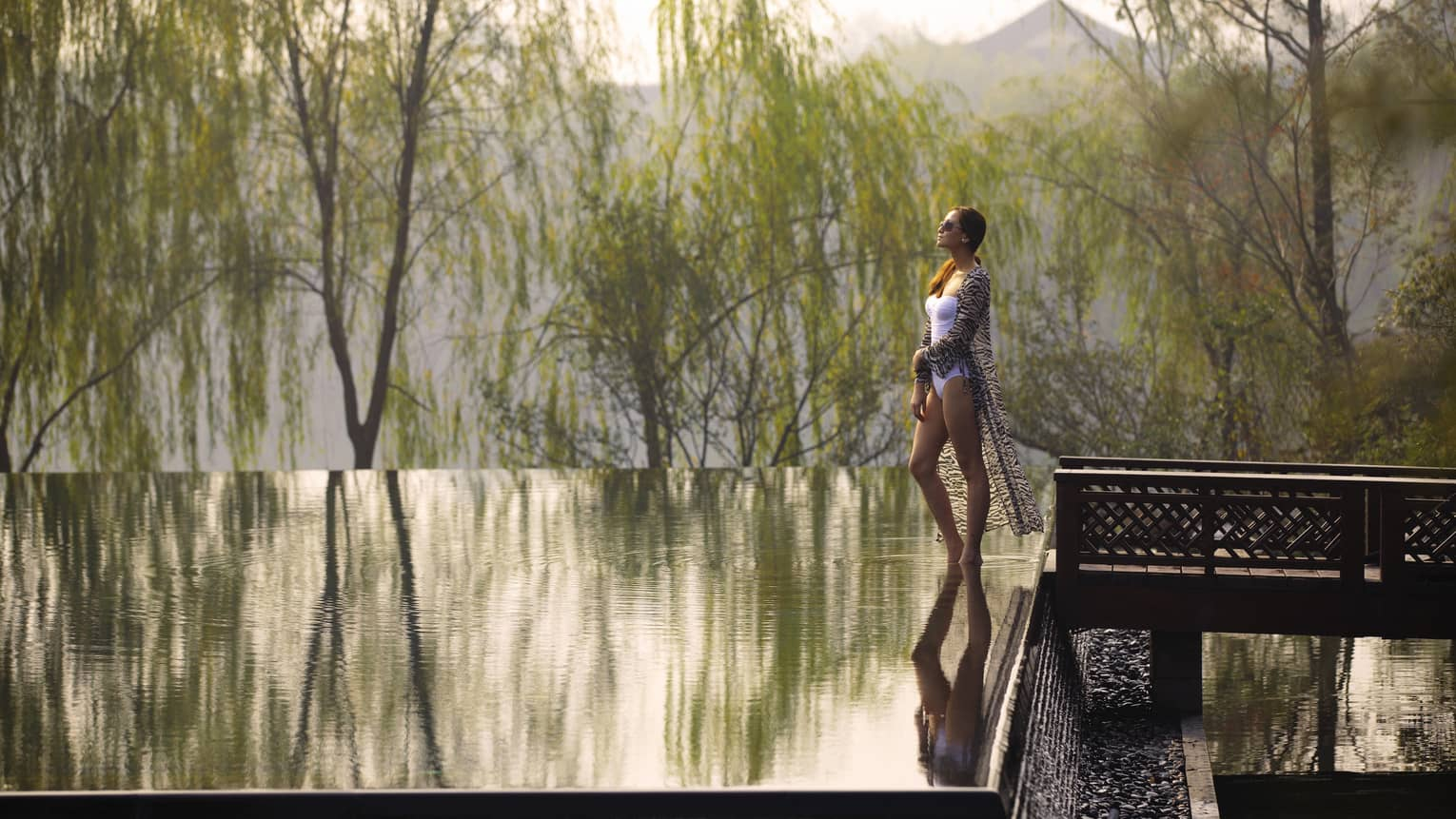 Woman wearing swimsuit, sheer cover walks by infinity swimming pool, water reflecting trees