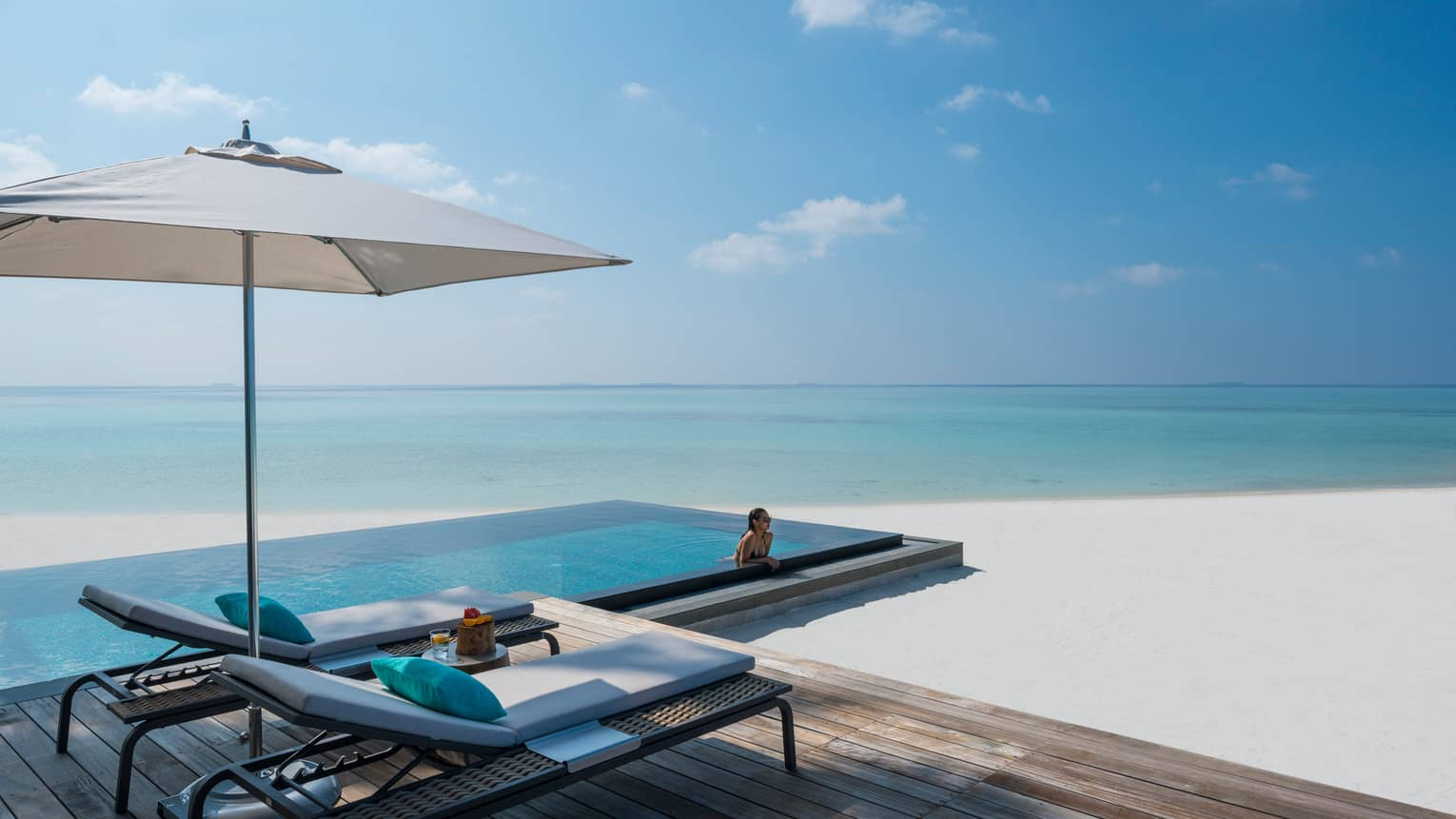 Woman leans against ledge of private infinity pool off Beach Villa patio, beach