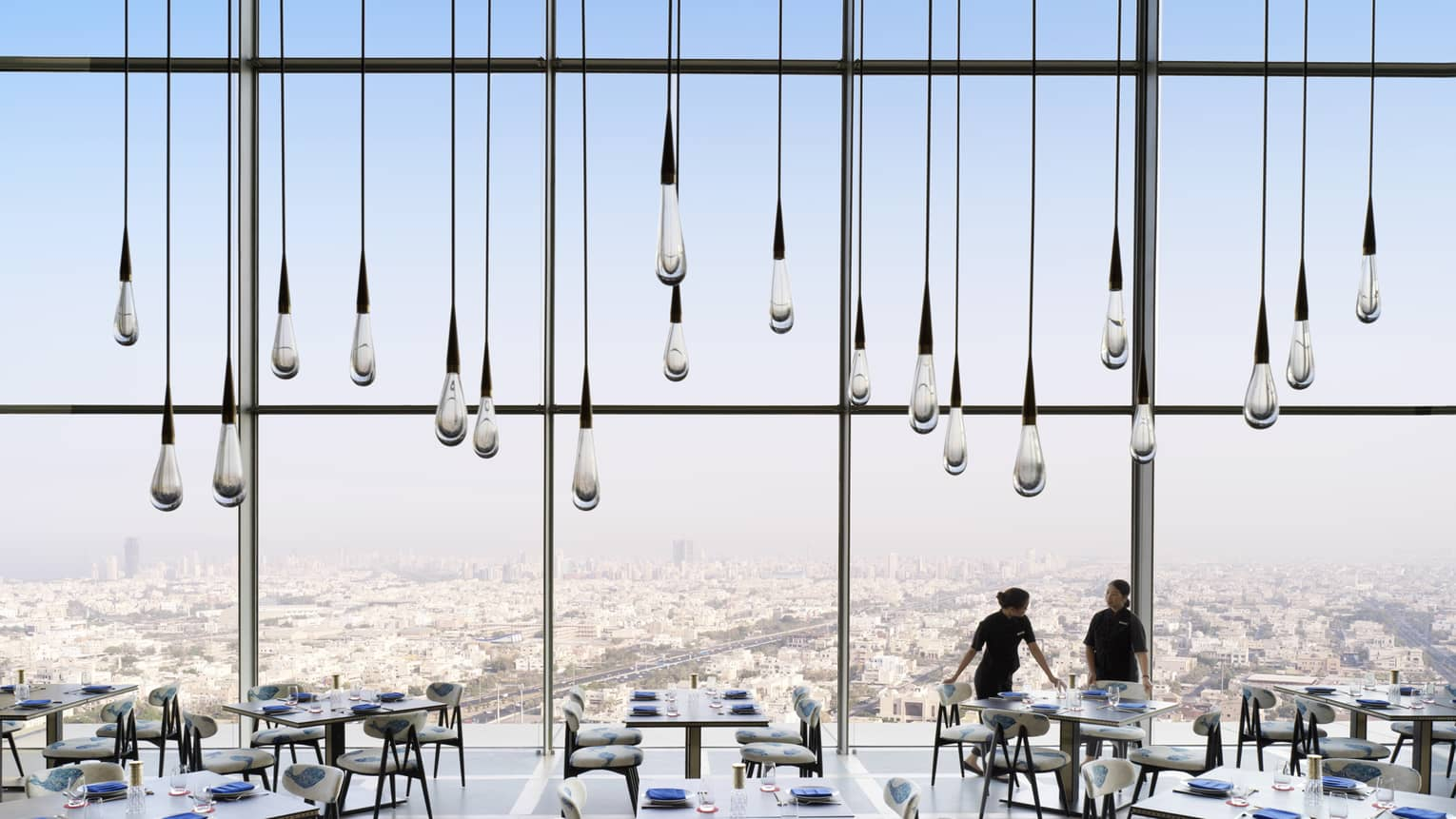 Row of raindrop-shaped glass hanging lights in front of floor-to-ceiling dining room window