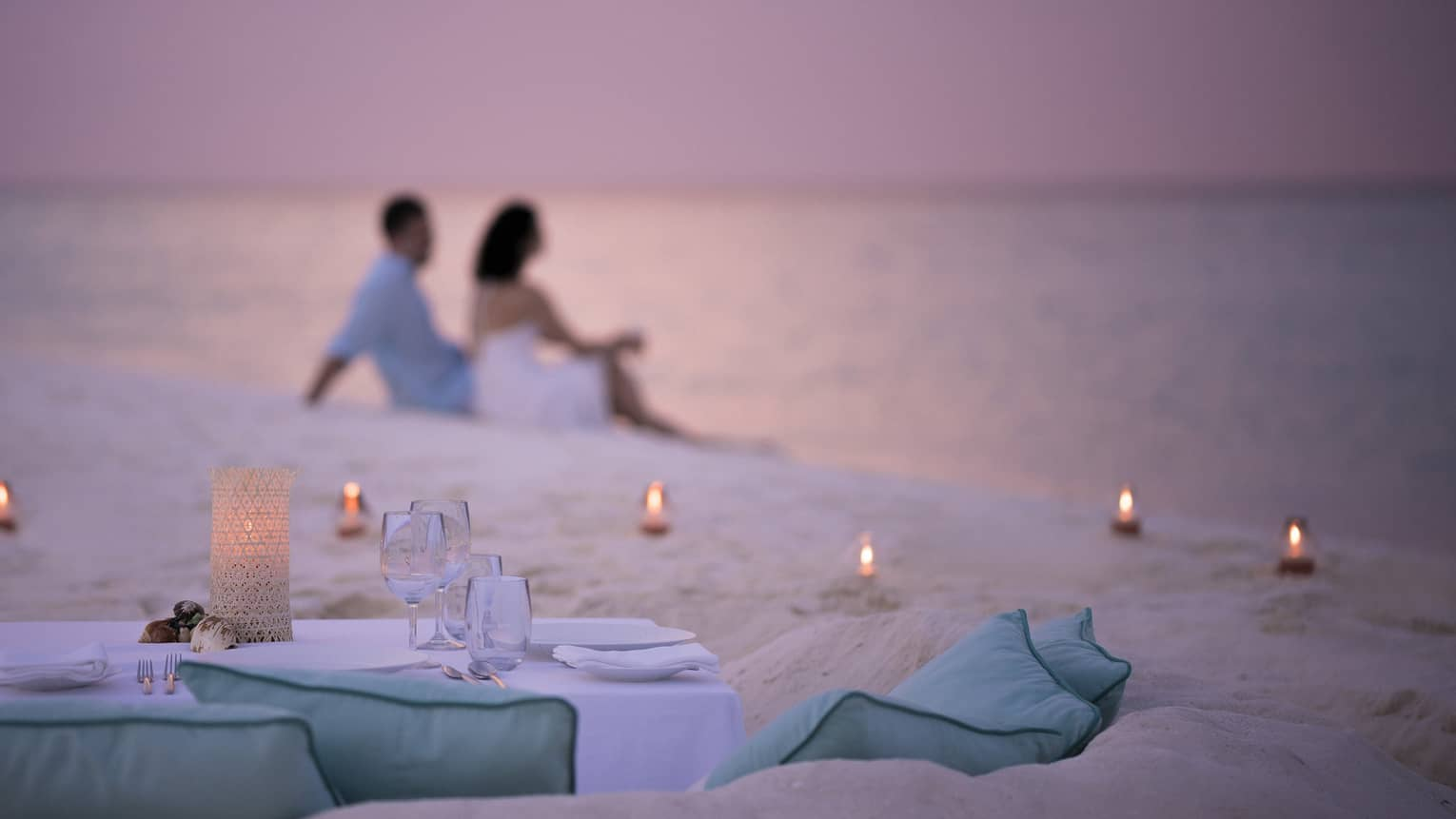 Private dining table in front of sand beach with tealight candles, couple sitting in sand