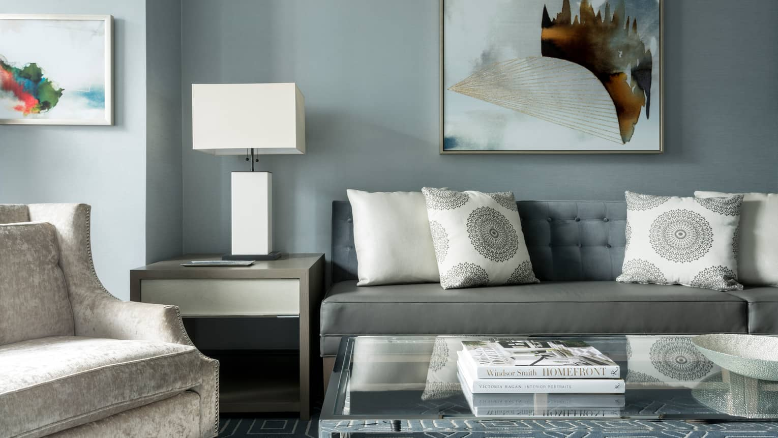 Midtown Suite long grey sofa with white accent pillows below abstract painting, table, lamp, armchair