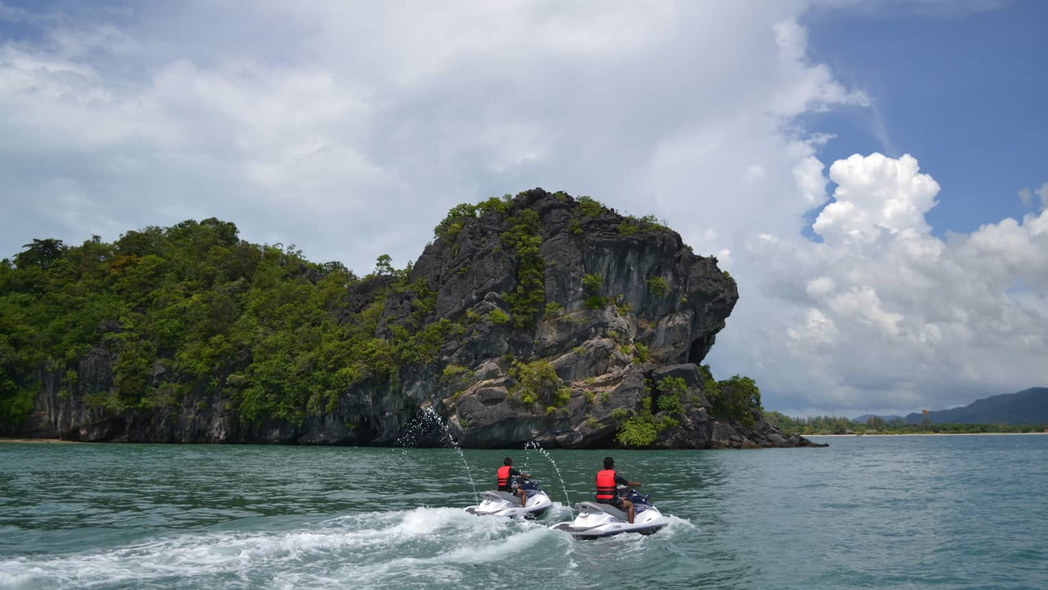 Two people wearing red life vests on jet skis ride on ocean under mountain