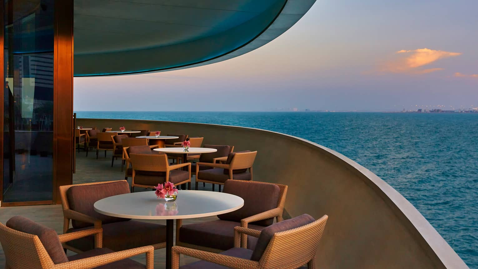 Dining tables on curved patio of Noby Restaurant, overlooking blue sea