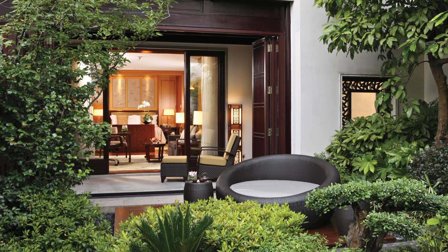 Grand Premier Room patio garden, large round black wicker chair, open villa door
