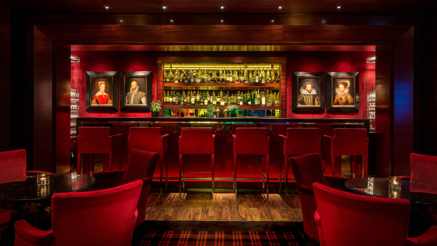 Dimly-lit Amaranto Bar with red accents, lighting, framed oil portraits on each side