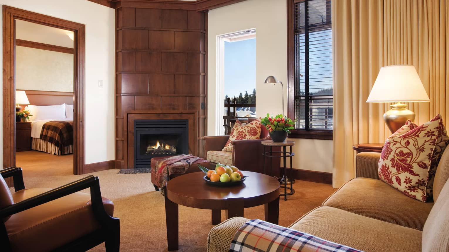 Executive Suite with wood panel fireplace between bedroom, patio doors, seating area, table with fruit bowl
