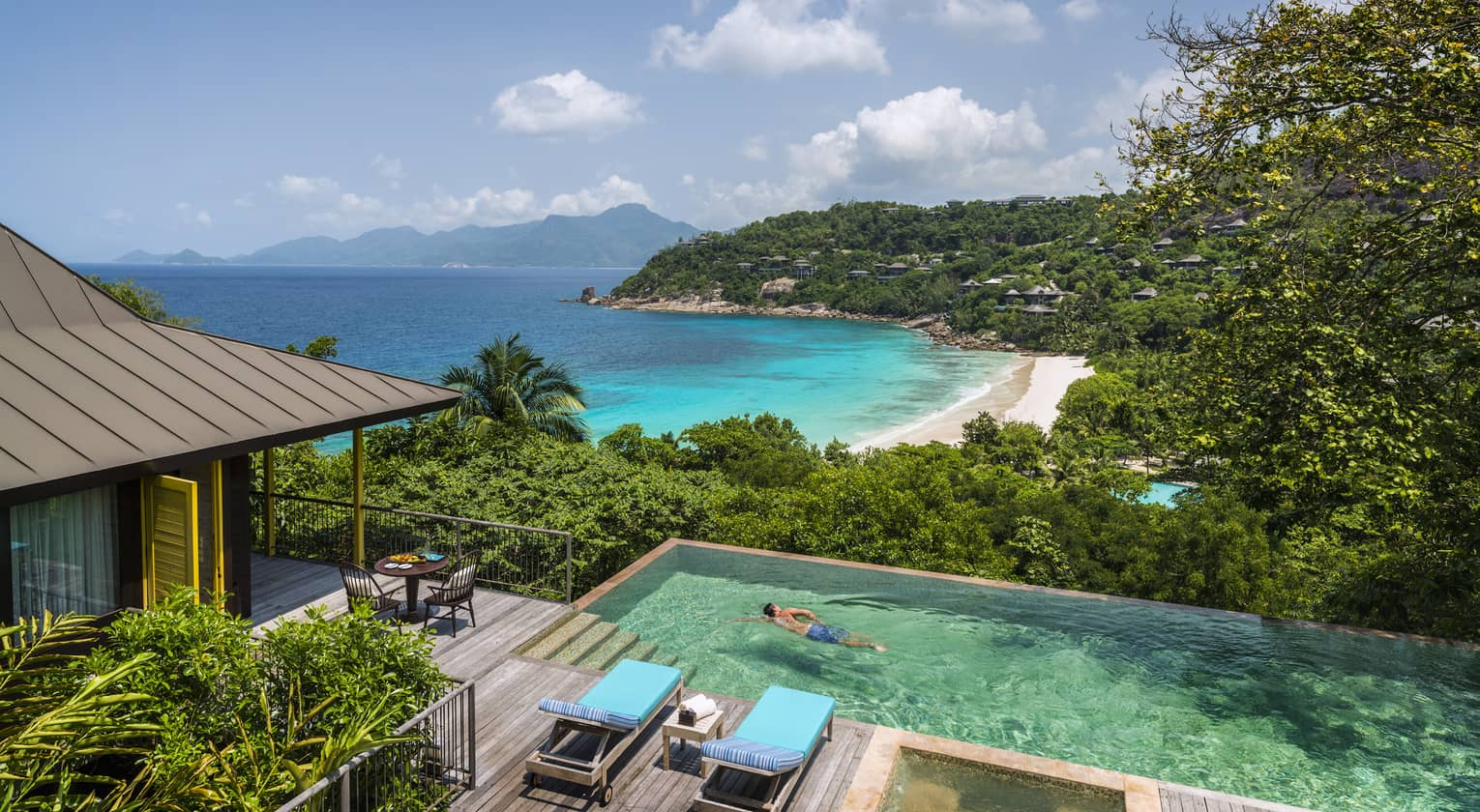 Two-bedroom Ocean View Suite deck, man swims laps in plunge pool, ocean and beach seen below