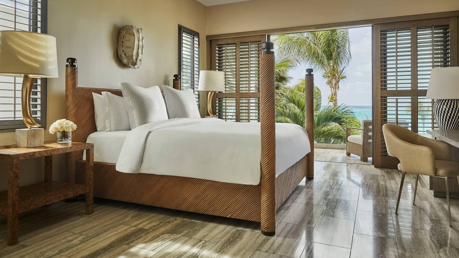 Four-bedroom Beachfront Villa wood poster bed, desk, sculpture on wall, open patio shutters to palms, ocean view