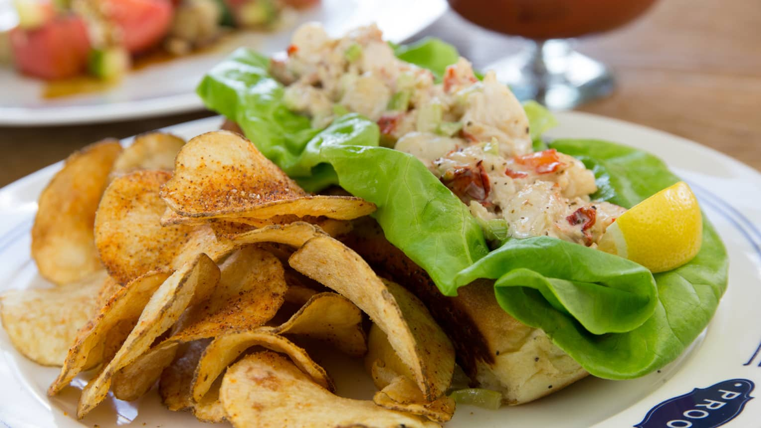 Maine Lobster Roll chopped lobster salad on bun, with green lettuce, potato chips on side