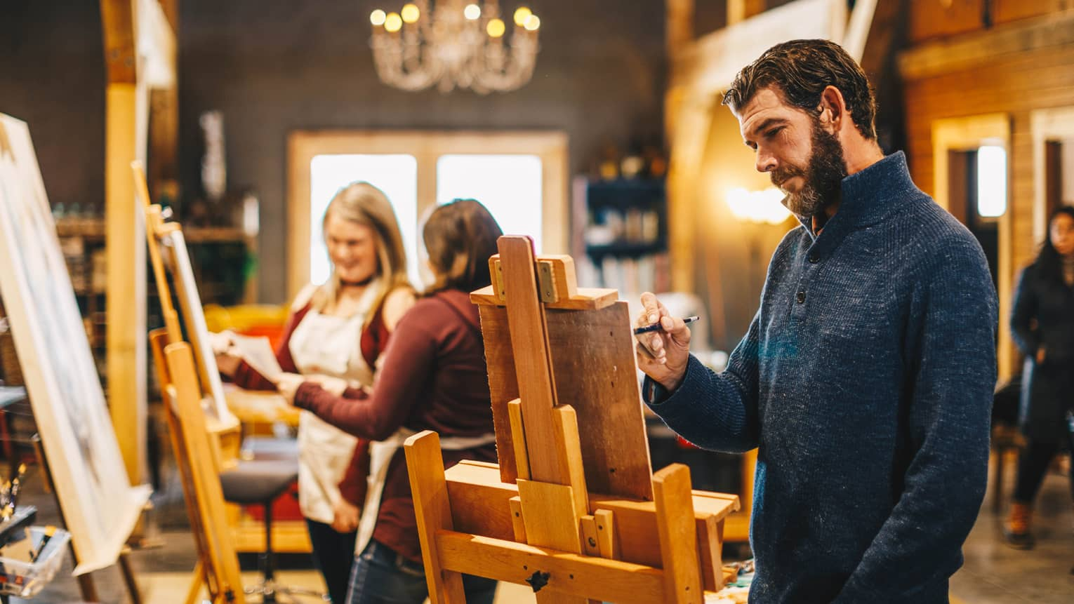 A man uses an easel and paints during a class