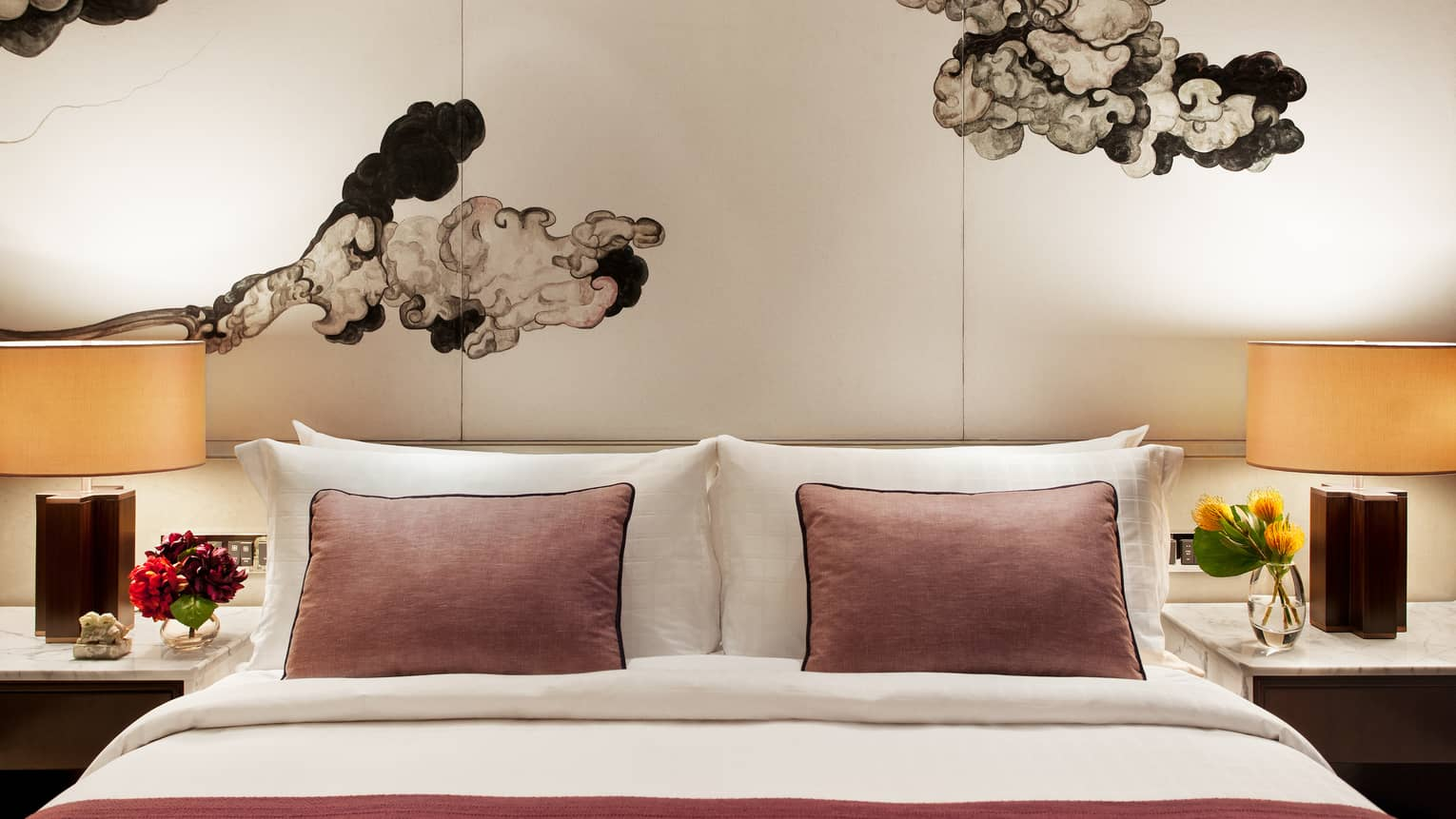 Club Grand Room hotel bed with pink accent pillows under Chinese brushwork mural