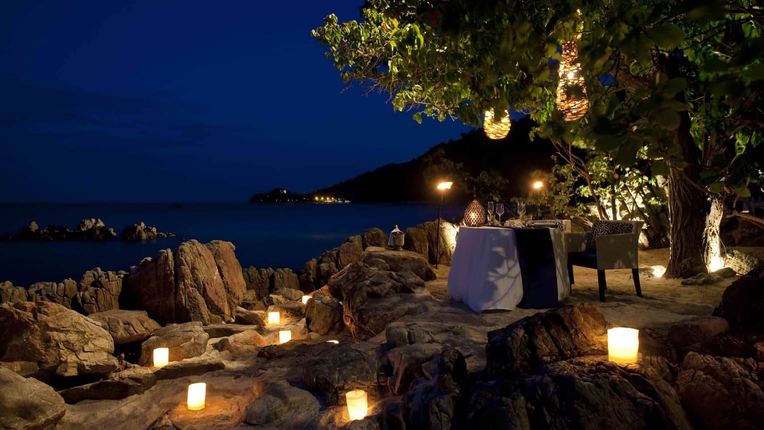 Candles glow on rocks near private dining table on beach at night