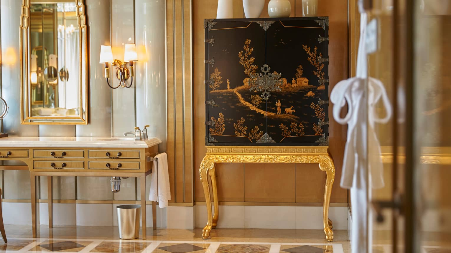 Elegant bathroom with patterned marble floors, large gold mirror over sink, chinoiserie cabinet topped with modern white vases