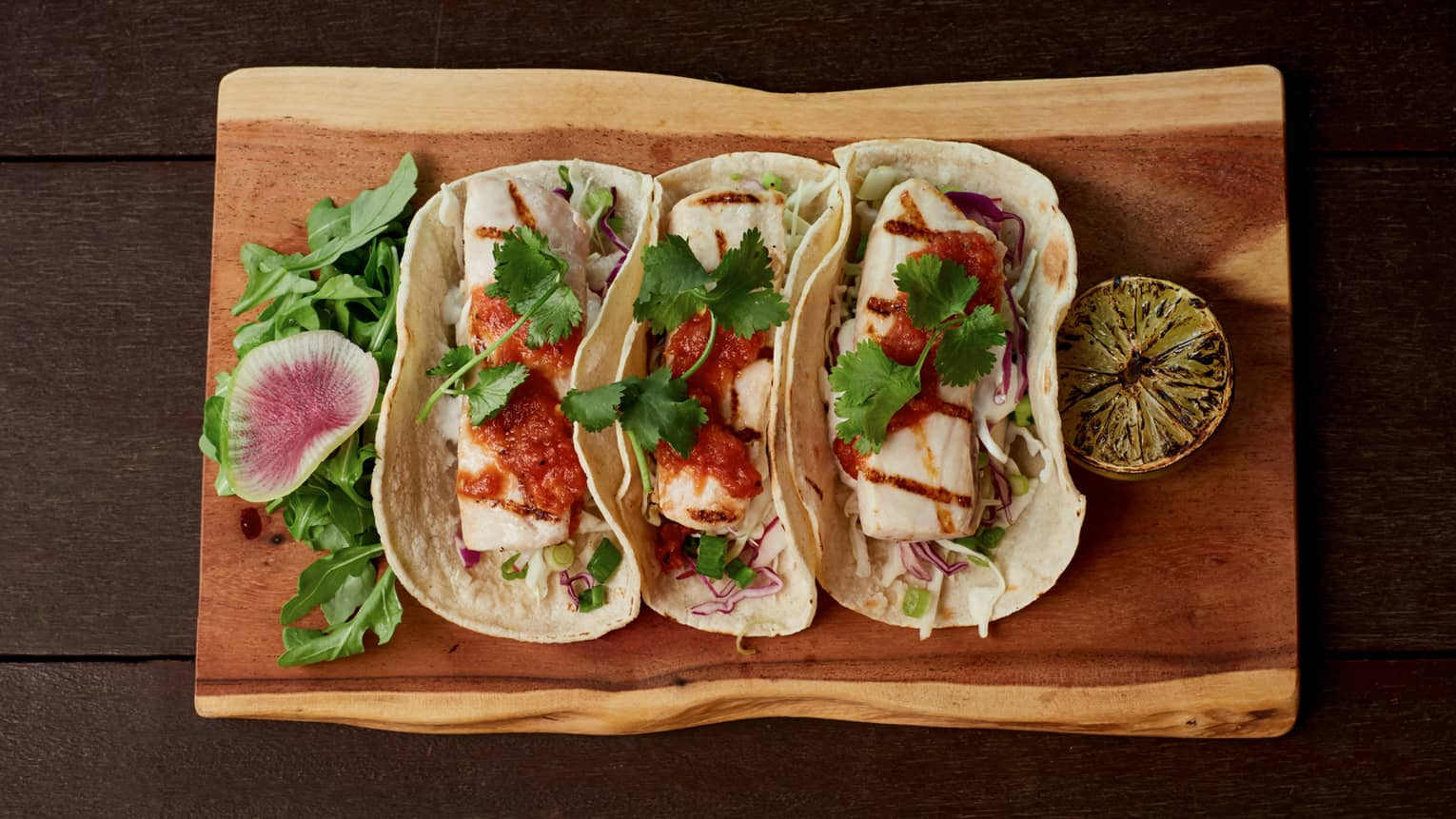 Aerial view of three large fish tacos, sauce on rustic wood platter
