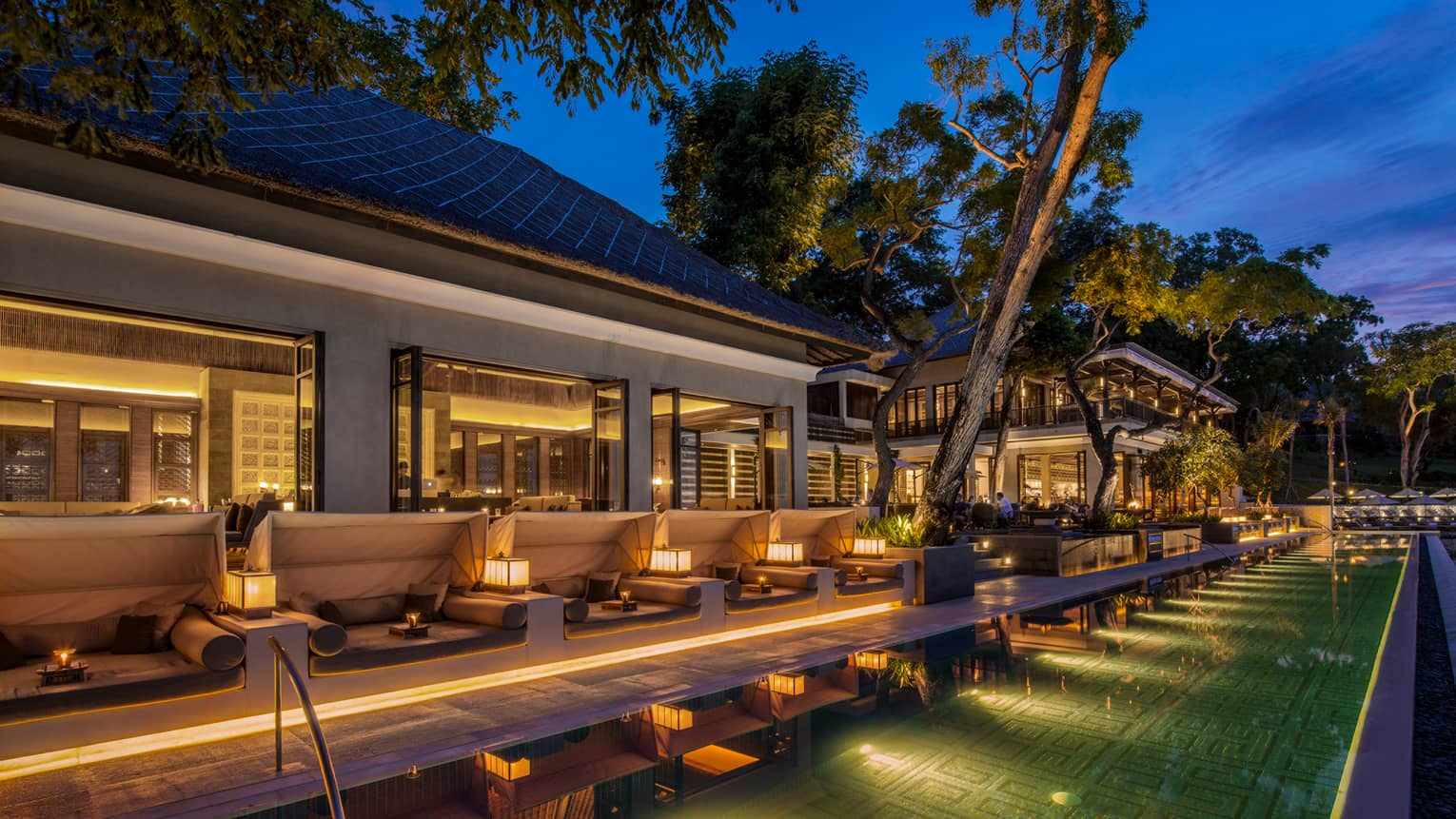 Sundara illuminated swimming pool at night lined with white patio sofas, candles