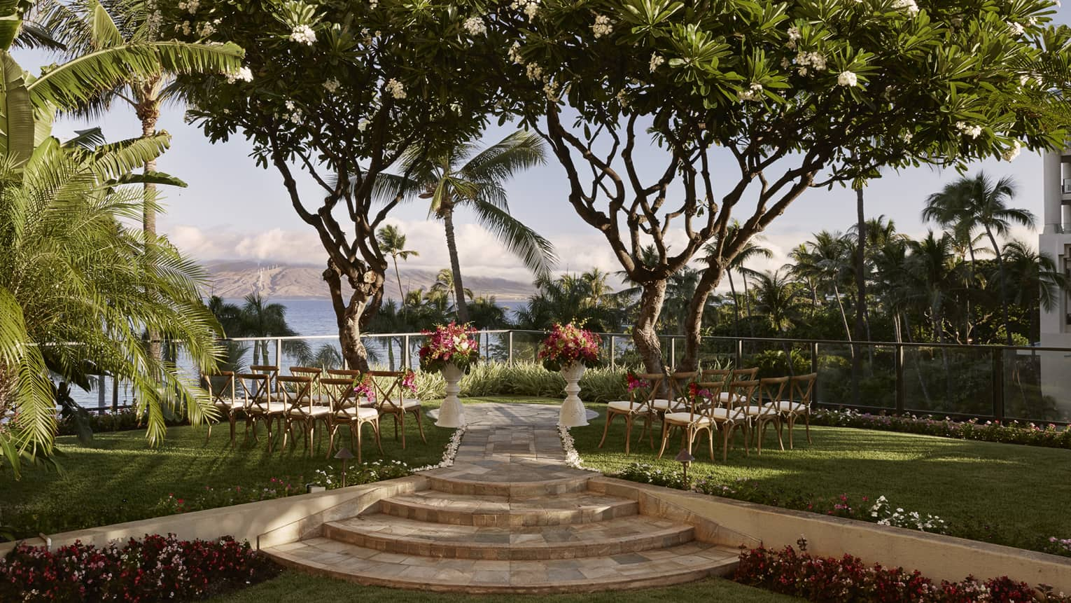 Outdoor wedding with chairs, flowers facing towards ocean and island, surrounded by trees