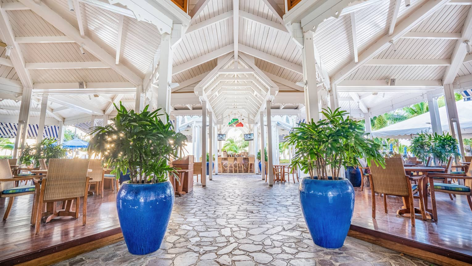 Cabana patio dining room under white cathedral ceilings, large blue pots, plants