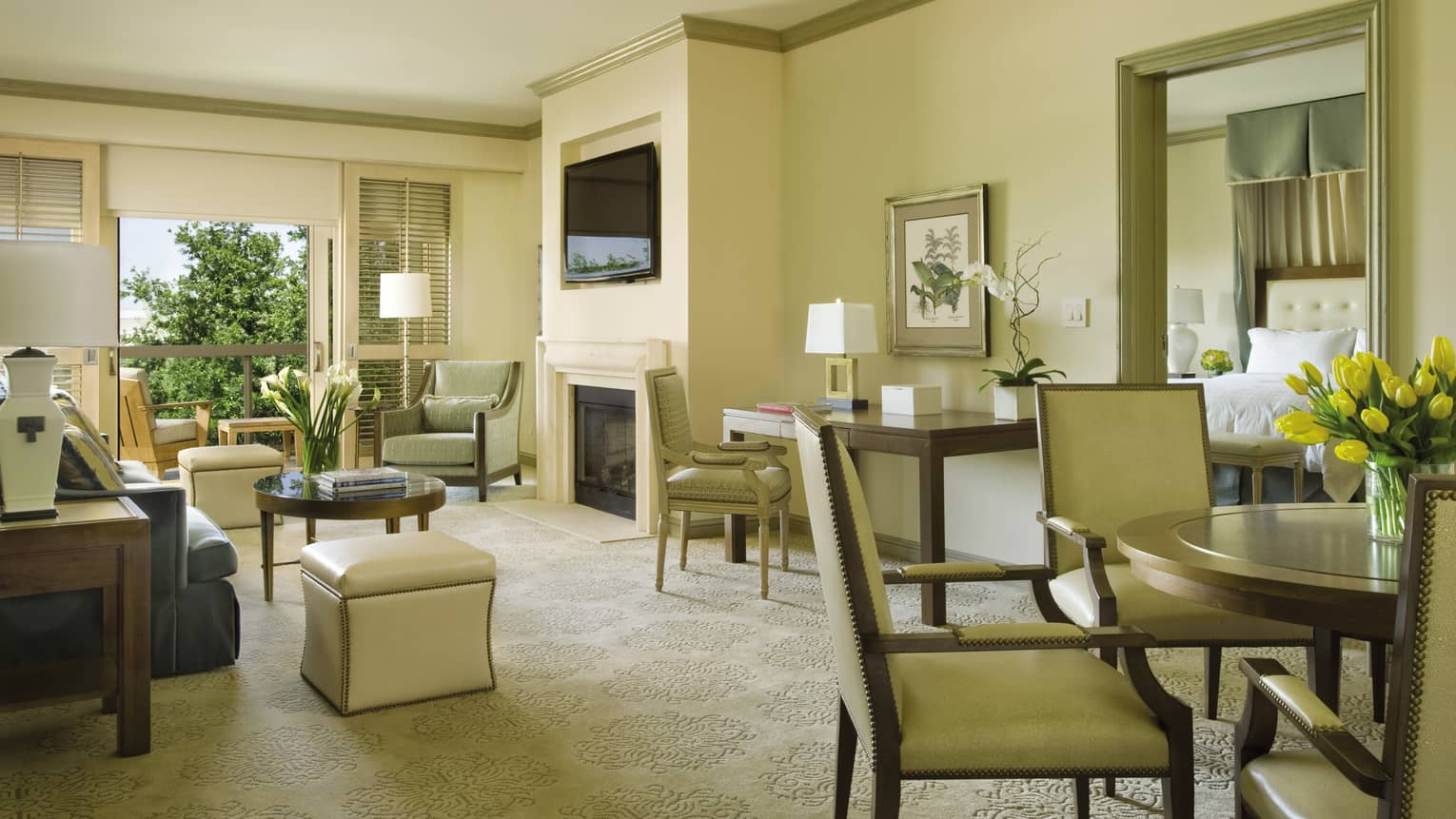 Premier Villa Suite round dining table, chairs by seating area with work desk, white fireplace