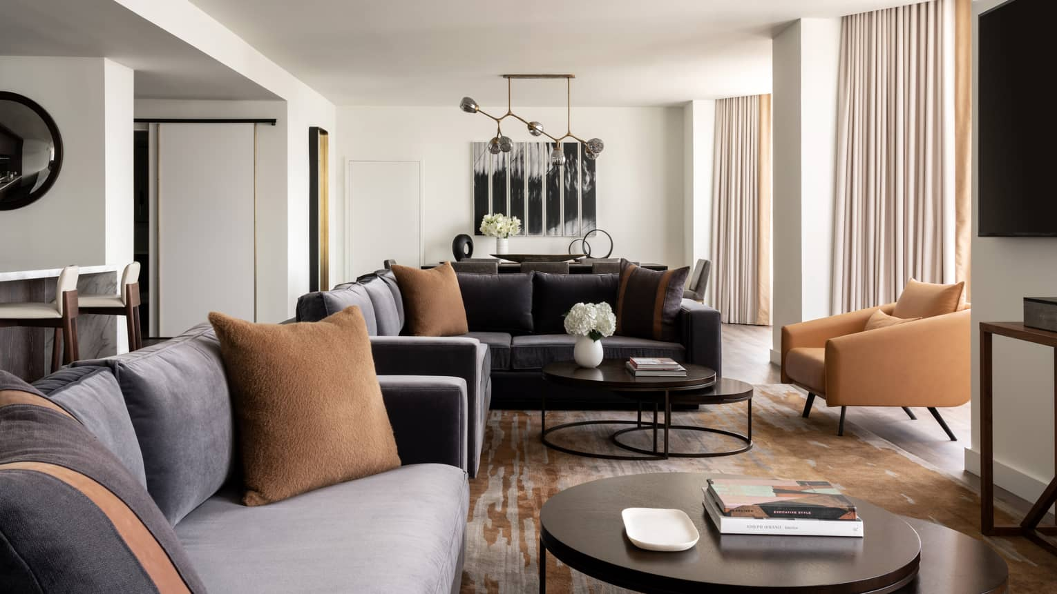 Living room with two grey-blue velvet sofas, tan leather arm chairs, round metal coffee table
