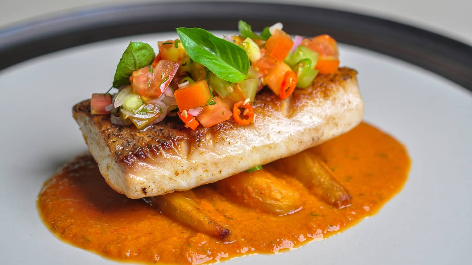 Ikan Rica Rica red snapper fillet topped with chopped vegetables, herbs and piquant dabu dabu sauce