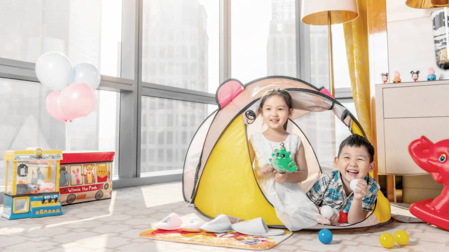 Two children play in a hotel room in Tianjin with windows facing the city