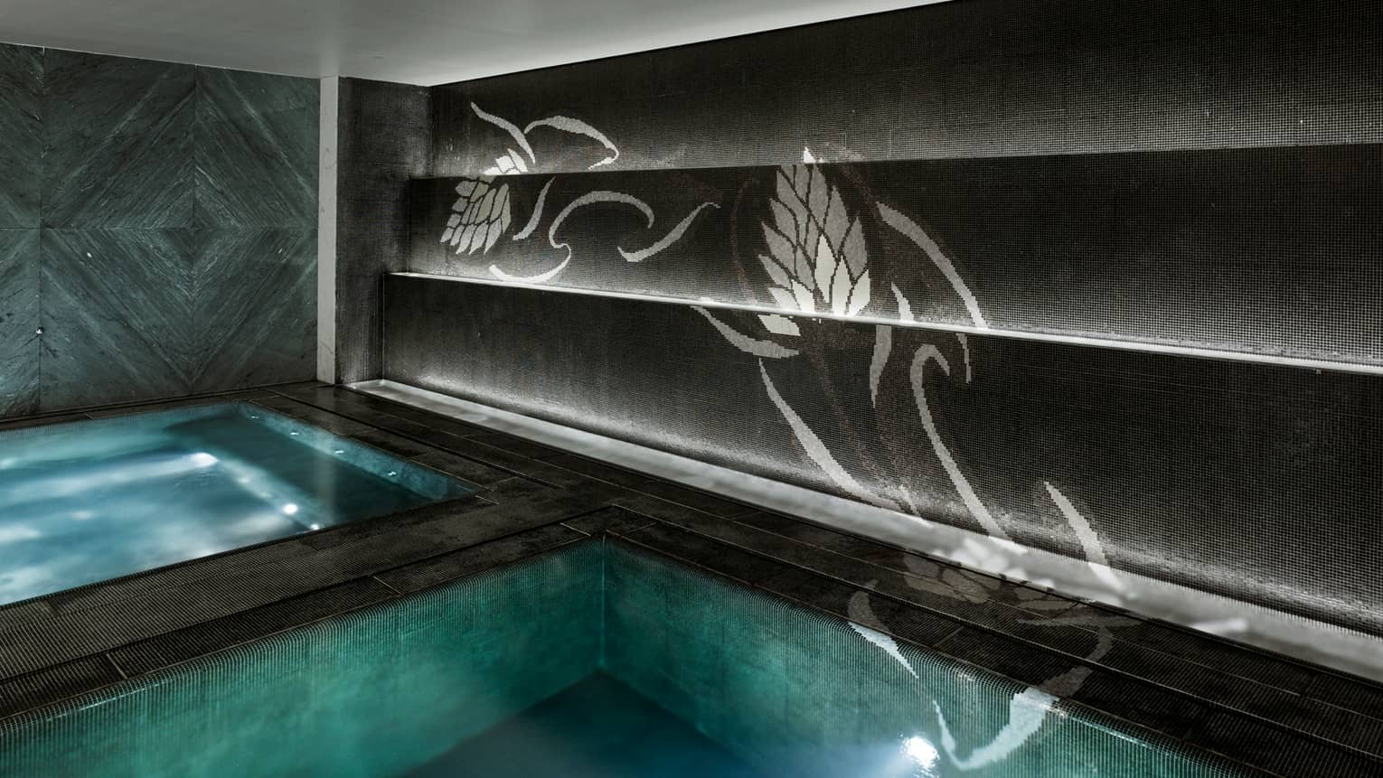 Spa hot tub with lights beside swimming pool under dark-paneled wall