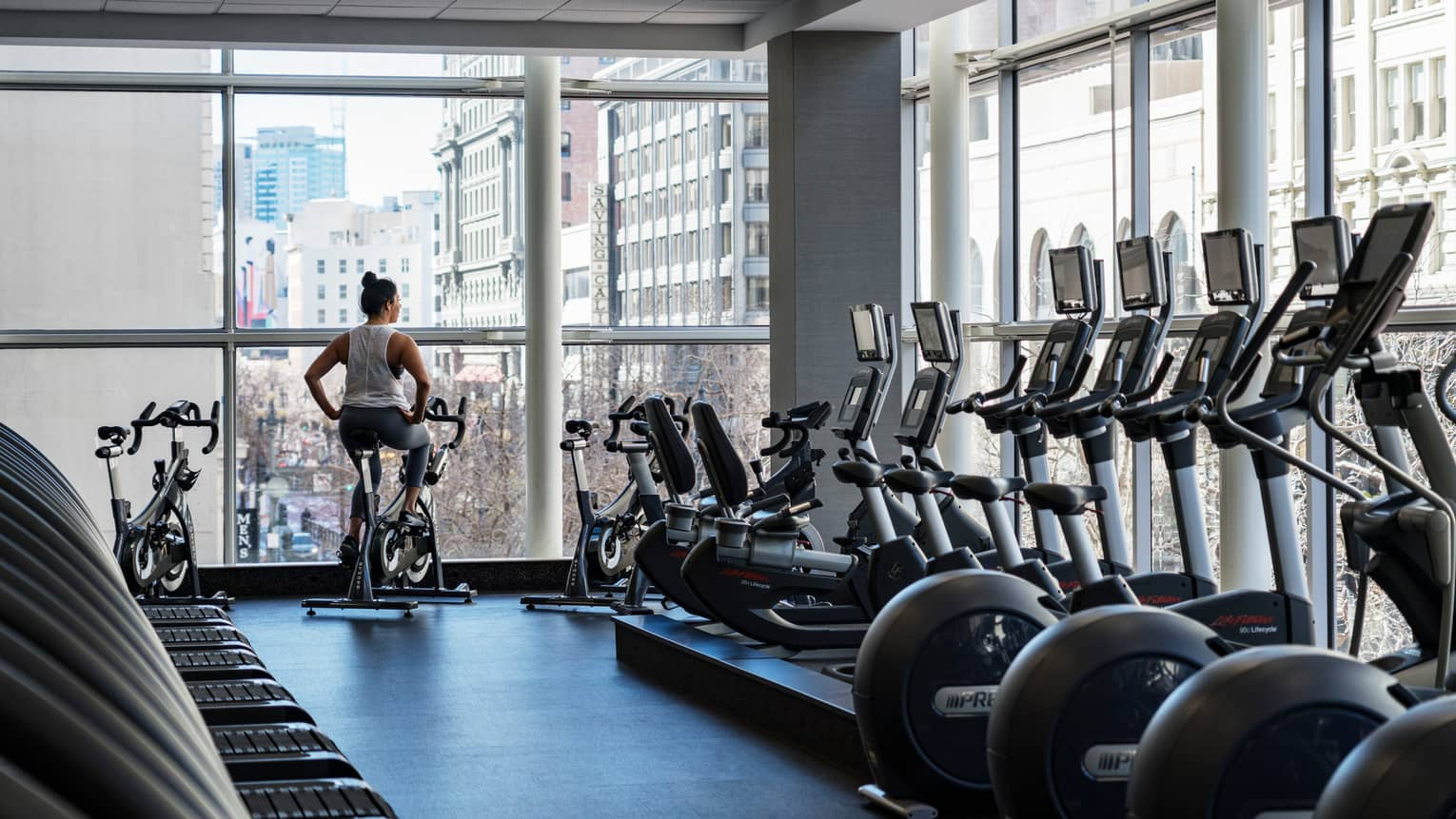 Equinox Fitness Centre, woman on exercise bike by floor-to-ceiling windows, row of cardio machines