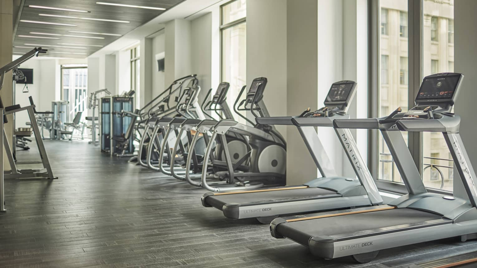 Treadmills, cardio machines in row by windows in Fitness Centre