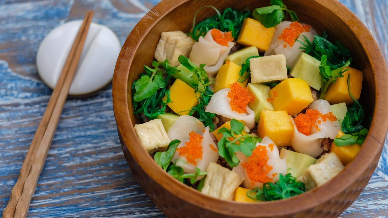 A wooden bowl full of colourful veggies and tofu, with wooden chopsticks resting on a porcelain dish beside it