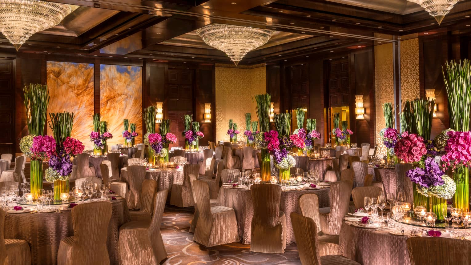 Imperial Ballroom wedding reception with fabric-covered chairs, floral centrepieces, crystal chandeliers